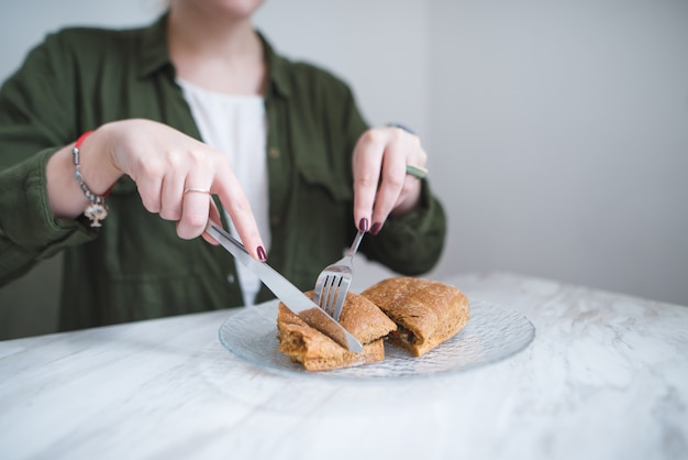 Szycie i nóż w rękach dziewczynki pokroić kanapkę w talerzu. kobieta je kanapkę w lekkiej restauracji.