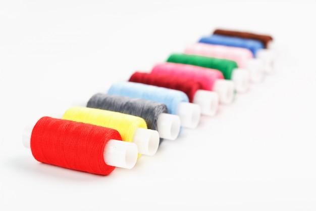 Szycie nici w różnych kolorach na szpulach na białym tle.