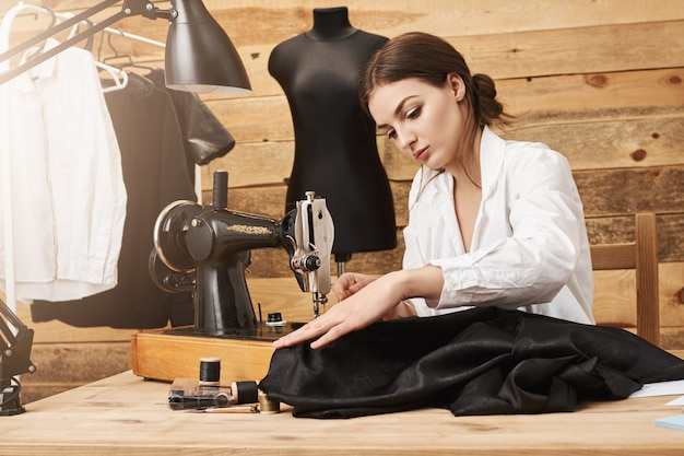 Szycie to nie tylko praca, to spryt. kreatywna projektantka pracująca z maszyną do szycia pod nową linią odzieży, skupiając się i wkładając wysiłki, aby wyglądała świetnie, będąc we własnym warsztacie