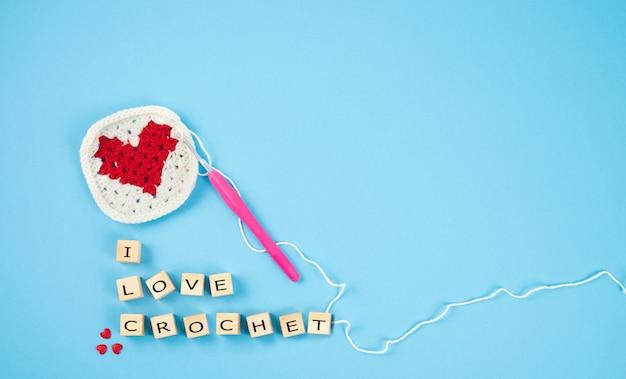 Szydełkowane czerwone serce. drewniane klocki z literami i love srochet. koncepcja rękodzieła.