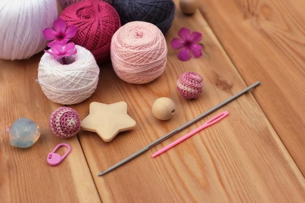 Szydełkowe różowe i szare haki i przędza, drewniane tło.