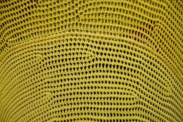 Szydełkowy wzór, zbliżenie prostego żółtego wzoru na drutach na tle