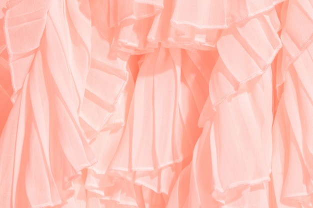 Szyfonowa tkanina w kolorze koralowym składa się z marszczeniami i falbankami.