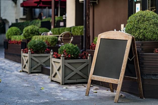 Szyld stojak tablica kawiarnia menu sklep restauracja z krzewami w doniczkach na zewnątrz