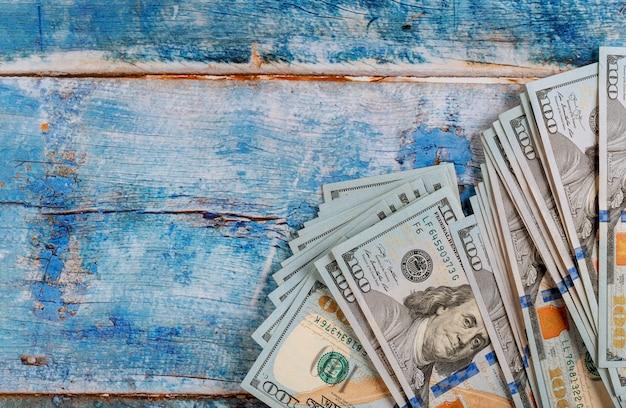 Szyldowi pieniądze gotówki amerykańscy dolary w błękitnym starym drewnianym stole