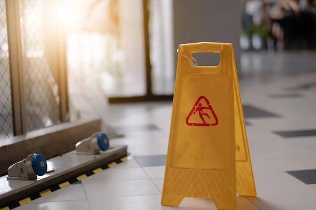 Szyldowy pokazuje ostrzeżenie ostrożność mokra podłoga w lotnisku.