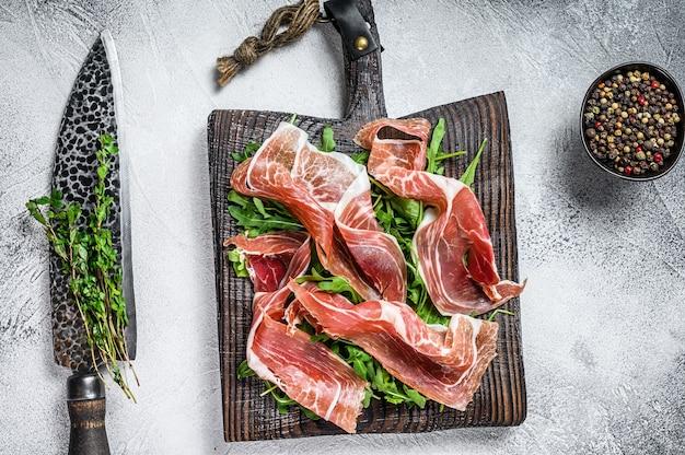 Szynka hiszpańska jamon serrano lub prosciutto crudo parma w plastrach. biały stół. widok z góry.
