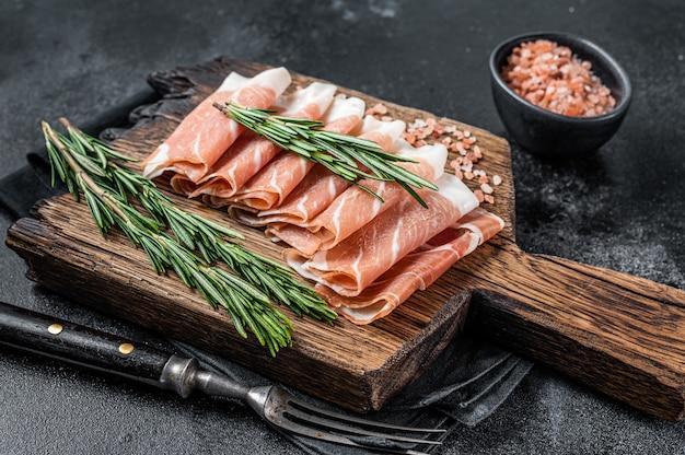 Szynka parmeńska prosciutto crudo, wieprzowina peklowana na sucho na drewnianej desce. czarny stół. widok z góry.
