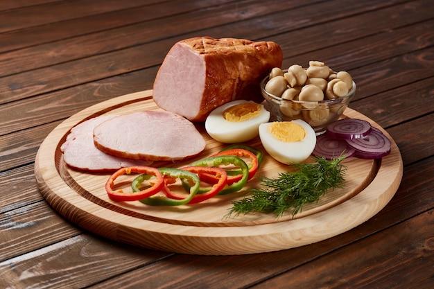 Szynka przyozdobiona warzywami, owocami i ziołami z sosami i chlebem na drewnianym talerzu na ciemnym drewnianym stole.