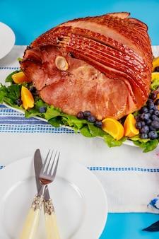 Szynka wędzona na spirali z hikory ze świeżą pomarańczą i jagodami. świąteczny posiłek.