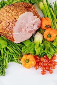 Szynka wieprzowa glazurowana ze świeżymi warzywami. zdrowe jedzenie. posiłek wielkanocny.