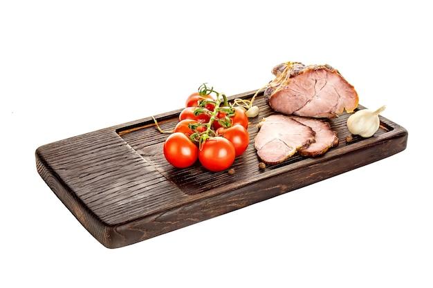 Szynka wieprzowa na drewnianej desce do krojenia ze świeżą sałatą i warzywami.