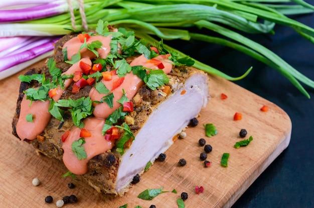 Szynka wieprzowa pieczona w dużych kawałkach z zieloną cebulą i sosem na desce do krojenia