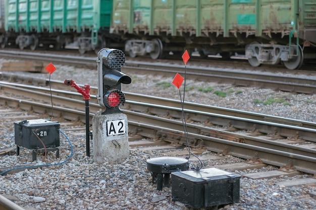Szyny z wagonami towarowymi w tle i semaforem ze świecącym czerwonym światłem na pierwszym planie. selektywne skupienie się na semaforze. tło z wagonami zamazane.