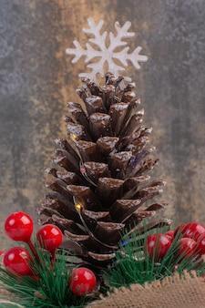 Szyszka ozdobiona holly jagodami i płatkiem śniegu na białym stole.