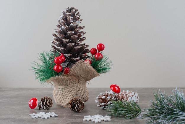 Szyszka ozdobiona jagodami ostrokrzewu i gałęziami na marmurowym stole.