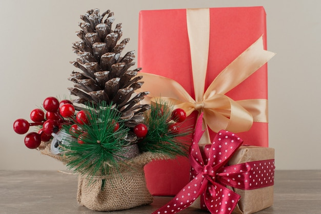 Szyszka ozdobiona jagodami ostrokrzewu i torebkami z prezentami na marmurowym stole.