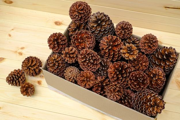 Szyszka umieszczona w tekturowym pudełku na drewnianym stole