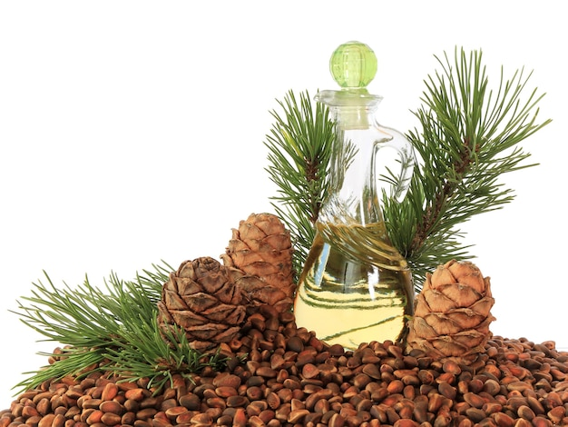 Szyszki cedrowe, orzechy i olej cedrowy w przezroczystej butelce na białym tle