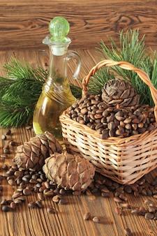 Szyszki cedrowe, orzechy i olejek cedrowy w przezroczystej butelce na drewnianym stole