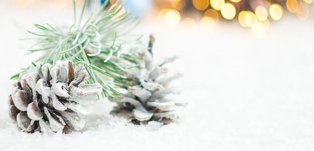 Szyszki i gałąź świerku pokryte śniegiem na tle niewyraźnych świateł girlandy boże narodzenie koncepcja
