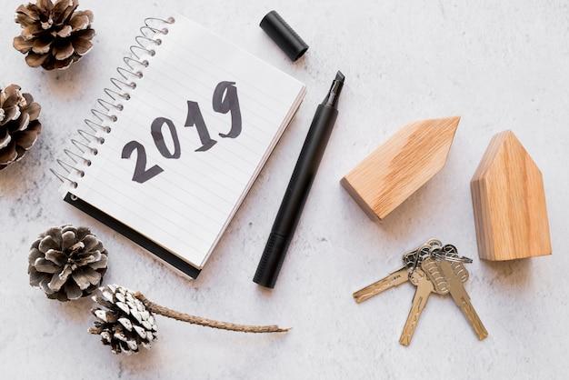 Szyszki sosnowe; klawiatura; drewniane domki i 2019 napisane na notatniku z pisakiem na białej, teksturowanej powierzchni