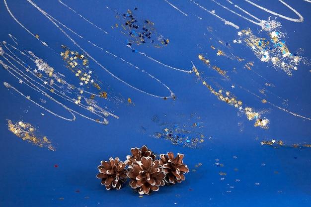 Szyszki sosnowe na niebieskim ozdobnym zimowym tle z iskierkami i gwiazdami (zachowanie tekstury niebieskiego kartonu)