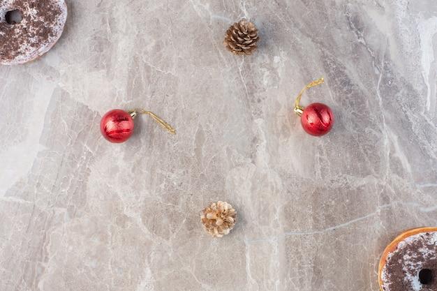 Szyszki sosnowe, świąteczne dekoracje i przeciwnie ustawione pączki na marmurze.