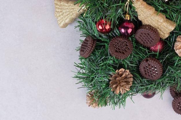 Szyszki z bombkami i ciasteczkiem na białej powierzchni