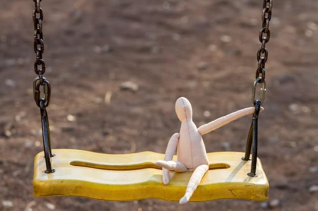 Szyta lalka bez twarzy siedzi na huśtawce i przylega do łańcucha.