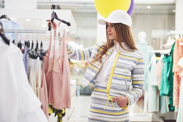 Ta sukienka jest idealna. młoda piękna uśmiechnięta kobieta dokonuje wyboru podczas zakupów w sklepie.