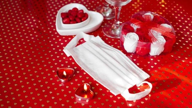 Tabela koncepcji walentynki. romantyczna kolacja z maską medyczną. koronawirus 2021. maska ochronna na twarz i czerwone nakrycie stołu
