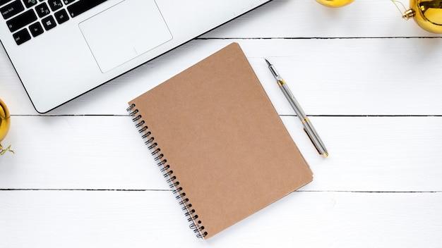 Tabela ze stylem życia. laptop, notatnik z długopisem na drewnianym tle. widok z góry