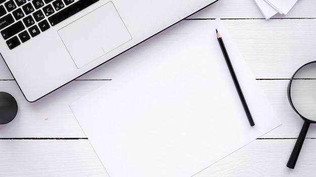Tabela ze stylem życia. laptop, papier ołówkiem i szkło powiększające z drewnianym tłem. widok z góry