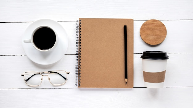 Tabela ze stylem życia. notatnik, filiżanka kawy, szklanki i długopis. widok z góry