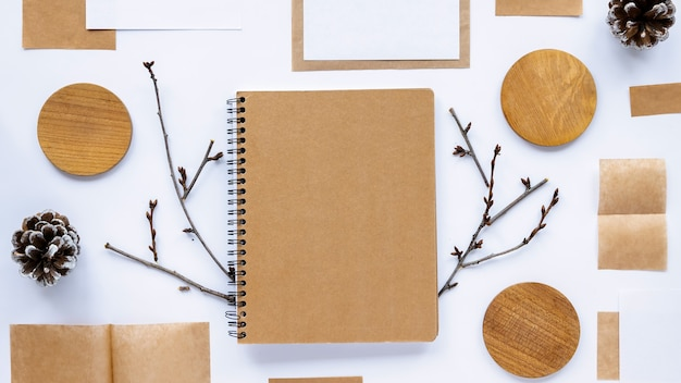 Tabela ze stylem życia. notatnik z ozdobnymi papierami, tablicami, gałązkami. widok z góry
