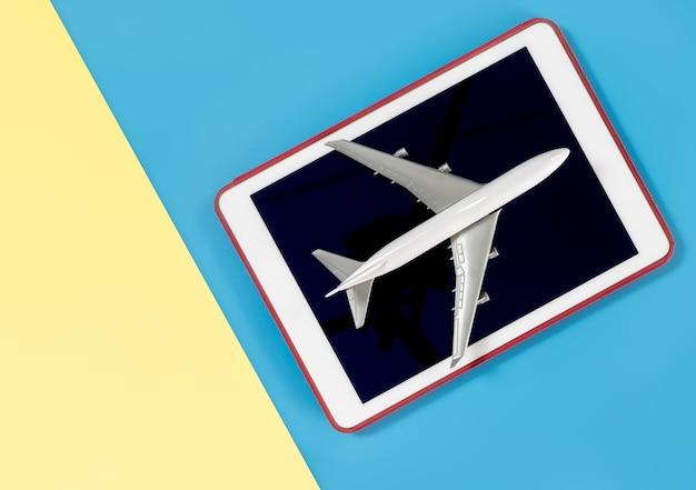 Tablet do kopiowania miejsca z samolotem do koncepcji podróży na niebieski żółty różowy