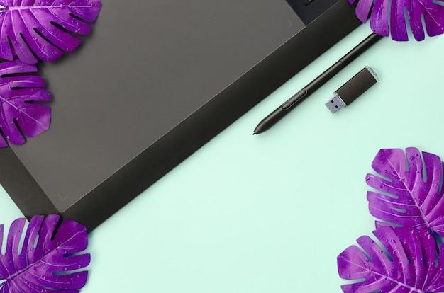 Tablet graficzny i długopis, karta pamięci i liście monstera