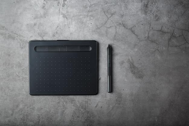 Tablet graficzny z rysikiem na ciemnym tle tekstury, widok z góry. gadżet do pracy jako projektant, artysta i fotograf