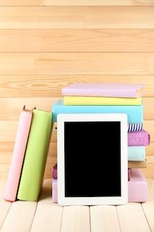 Tablet pc i książki na drewnianym stole, na drewnianej powierzchni