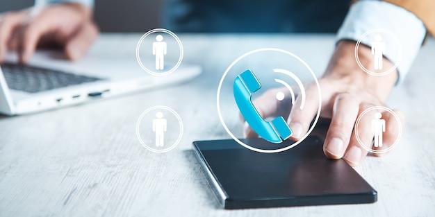 Tablet ręka człowieka z ikoną telefonu i osób na ekranie