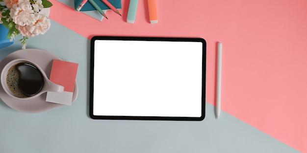 Tablet z białym ekranem i różne sprzęty stawiają na dwukolorowym stole