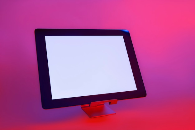 Tablet z białym ekranem na tle twórczego światła. w kolorowych, jasnych neonowych niebieskich i fioletowych światłach uv.