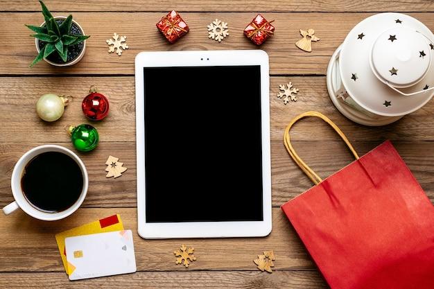 Tablet z czarnym ekranem, filiżanka kawy, karta debetowa, dekoracje świąteczne, płatki śniegu na drewnianym stole