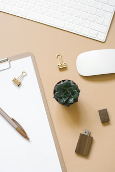 Tablet z czystą kartką papieru na beżowym tle, stolik z komputerem i zapasami