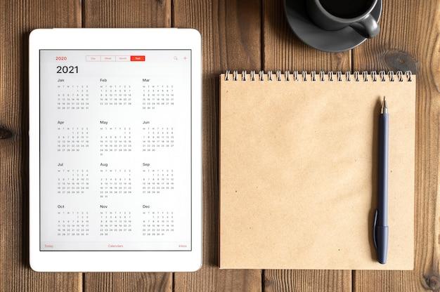 Tablet z otwartym kalendarzem na 2021 rok, filiżanką kawy i notesem z papieru kraftowego na tle stołu z desek