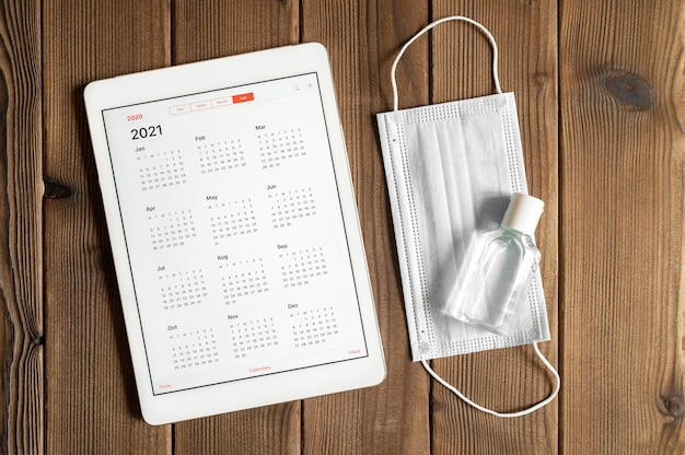 Tablet z otwartym kalendarzem na 2021 rok oraz ochronną maską medyczną i środkiem dezynfekującym do rąk na tle stołu z drewnianych desek. koncepcja ochrony przed koronawirusem covid-19 w 2021 r.