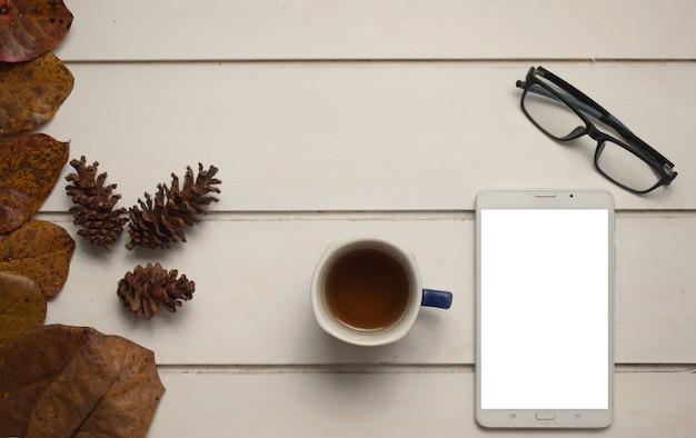 Tablet z pustym ekranem dla tekstu lub obrazu i filiżankę herbaty na drewnianym tle. widok z góry