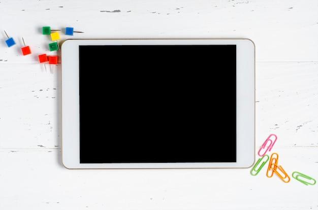 Tablet z pustym ekranem i artykułami biurowymi na białym drewnie