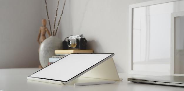 Tablet z pustym ekranem w białym minimalnym obszarze roboczym z artykułami biurowymi